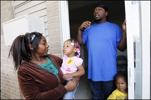 Jasmine Taylor holds daughter Kale-Jah Williams, 2, as Travis Williams speaks about the little girls' asthma proplems at apartment at Greenbelt Apartments. At right is the couple's other child, son Keontea Taylor, 2. The pair believe Kale-Jah's asthma problems are related to the cockroaches in their apartment.