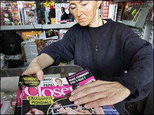 A news stand worker checks copies of Closer magazine in Nice, southern France, Tuesday.