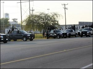 A group of Mexican federal police stand in front of the prison in Piedras Negras, Mexico Monday. Authorities say 132 inmates have escaped from this jail in northern Mexico, sparking a search by federal police and soldiers in an area close to the U.S. border.