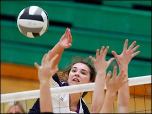 Notre Dame's Madeline Smyth spikes the ball against  Clay's Madison Phillips (23) and Lydia Winckowski (2).