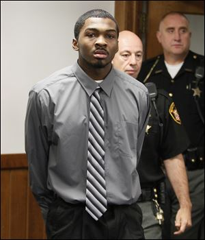 Charles Toyer is escorted into Lucas County Common Pleas Court in Toledo for the start of his trial, Monday, September 17, 2012. He is charged with the stabbing death of Tiffany Wilborn.