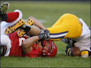 Bedford High School player Scott Szakovits, 32, tackles Saline High School player Caleb Luckett, 15.