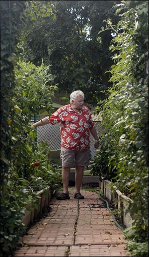 Mike Monus stands in his backyard garden that has raised-beds to accommodate his physical limitations.