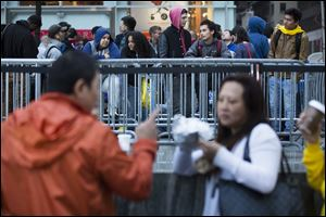 Consumers wait in line outside the Fifth Avenue Apple store for the imminent release of the iPhone 5, on Friday, in New York. Hundreds of people waited in line through the early morning to be among the first to get their hands on the highly anticipated phone.