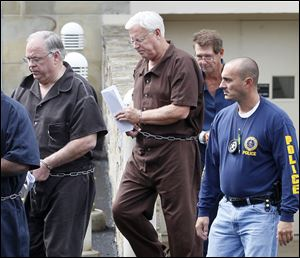 U.S. marshals escort, from left,  Bradford L. Huebner, of Ottawa Hills, Michael L. Teadt, of Maumee, and Charles N. Emmenecker, of Sylvania, from U.S. District Court in Toledo following their arraignment, Thursday, Sept. 20. They are charged on allegations that they were involved in a $24 million fraud scheme involving the sale of Iraqi dinar currency and two non-existent hedge funds.