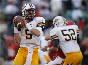 Saline High School quarterback Tyler Palka looks to throw during the first quarter against Bedford High School in Temperance.