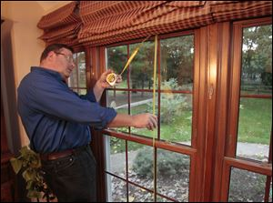 Mike Marchant of Arnold's Home improvement measures a window at the Sylvania Township home of Larry and Sharon Roan. The Roans had vinyl windows and a french door installed.
