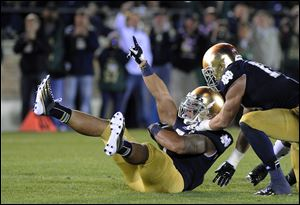 Notre Dame's Manti Te'o, left, reacts with Zeke Motta after Te'o makes an interception during the first half against Michigan Saturday in South Bend, Ind.