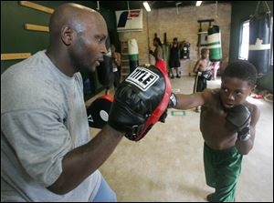 Head coach Gerald Carter works with National boxing champion Otha Jones III, 10, at the Soul City Boxing Gym in Toledo.