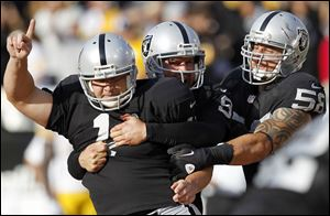 Oakland Raiders kicker Sebastian Janikowski  (11) celebrates with holder Shane Lechler (9) and  Dave Tollefson (58) after Janikowski's 43-yard field goal to win the game against the Pittsburgh Steelers during the fourth quarter of an NFL football game in Oakland, Calif. on Sunday.