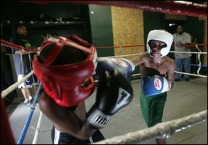 Ta'loun Nedd, 9, left, spars with national boxing champion Otha Jones III, 12, at the Soul City Boxing Gym in Toledo.