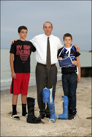 Erik Chappell of LaSalle Township, Mich., and and sons Grant, 14, left, and Cole, 12, gather with the casts Cole had to wear as a result of the car-bombing Sept. 20, 2011. All three were injured.