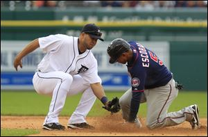 Minnesota Twins' Eduardo Escobar safely steals second under the tag of Detroit Tigers shortstop Jhonny Peralta during the fifth inning of a baseball game at Comerica Park in Detroit.