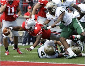 Ohio State's Braxton Miller scores a touchdown against Alabama-Birmingham's Jake Genus, bottom, and Lamar Johnson (6) during the second quarter Saturday in Columbus.
