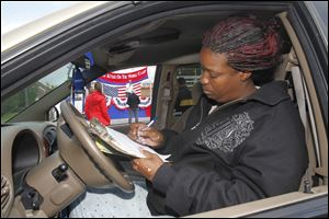 Toledo resident Lashonda Gaston re-registers, to reflect her address change, during the ToledoVotes! rally at Savage Park.