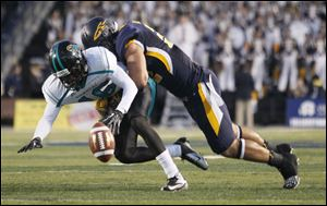 University of Toledo player Dan Molls, 32, hits Coastal Carolina player Tyrell Blanks, 16, causing an incomplete pass during the first quarter at the Glass Bowl, Saturday, September 22, 2012.