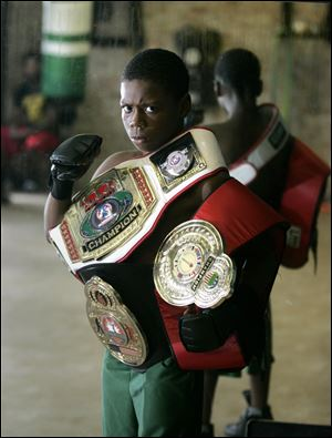 Toledoan Otha Jones III, 12, poses with three of his 10 national boxing tournament belts.