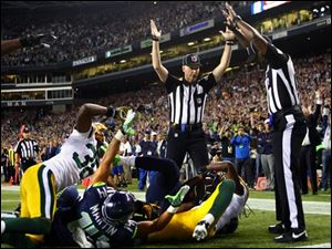 Officials signal after Seattle Seahawks wide receiver Golden Tate pulled in a last-second pass for a touchdown from quarterback Russell Wilson to defeat the Green Bay Packers 14-12 Monday.