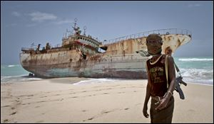 Masked Somali pirate Abdi Ali stands near a Taiwanese fishing vessel that washed up on shore after the pirates were paid a ransom and released the crew, in the once-bustling pirate den of Hobyo, Somalia.