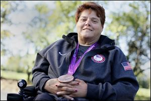 Zena Cole of Oregon relaxes at Pearson Metropark with the bronze medal she won in the discus throw at the 2012 Paralympics in London, which led to a meeting with President Obama and the First Lady.