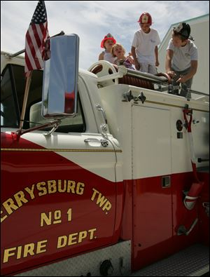 Children explore a truck during an open house in 2009. Department officials say extinguishing fires remains a high priority, but one of the biggest changes over the decades is in medical training for department personnel.