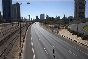 A woman runs along the car-free Ayalon expressway, during the holiday of Yom Kippur in Tel Aviv, Wednesday. Israelis are marking the holiday of Yom Kippur, or 'Day of Atonement,' which is the holiest of Jewish holidays when observant Jews atone for the sins of the past year and the Israeli nation comes to almost a complete standstill.