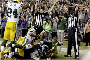 An official, rear center, signals for a touchdown by Seattle Seahawks wide receiver Golden Tate, obscured, as another official, at right, signals a touchback, on the controversial last play of an NFL football game against the Green Bay Packers in Seattle. The Seahawks won 14-12.