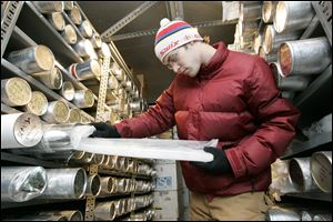 Graduate research associate Aron Buffen pulls an ice core from the deep-freeze storage unit.