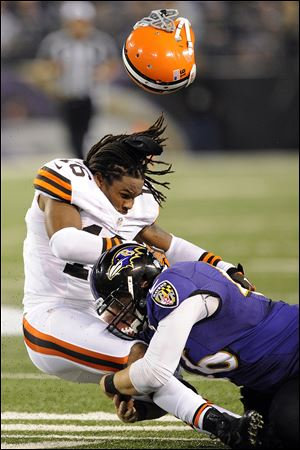 Ravens long snapper Morgan Cox tackles Browns wide receiver Josh Cribbs as his helmet is dislodged from a hit by another player during the first half tonight in Baltimore.