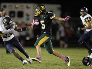 Clay's Anthony Ramirez (5) runs the ball against Whitmer defenders.