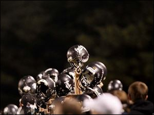 Perrysburg players raise their helmets during the fourth quarter of Friday night's home game against Sylvania Southview.