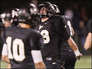 Perrysburg's junior linebacker Mark Delas, center, screams after tackling Southview's quarterback.