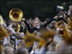 Perrysburg cheerleader Rachel Hess, 15, center, helps lead a squad of dozens of cheerleaders-in-training during the first quarter of Friday night's home game against Sylvania Southview. The children were on hand to help the varsity cheerleaders after participating in a cheering clinic earlier in the week.