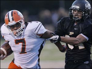 Southview's senior running back Ahmad Parker tries to evade a Perrysburg defender.