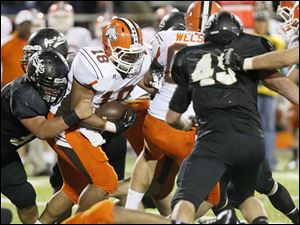 Southview's senior running back Jovan Palin struggles to make it past Perrysburg defensemen.