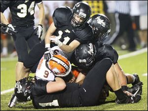 Perrysburg's junior defensive back Matt Mesker (11) helps take down Southview sophomore running back Keith Gilmore.