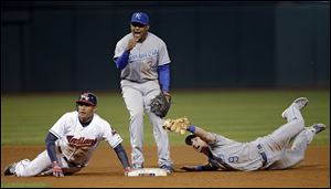Kansas City Royals shortstop Tony Abreu (34) and second baseman Johnny Giavotella (9) plead for an out after Cleveland Indians' Ezequiel Carrera dived back into second on a line out  Friday in Cleveland. Carrera was ruled safe.