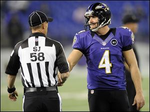 Side judge Jimmy DeBell shakes hands with Ravens punter Sam Koch.