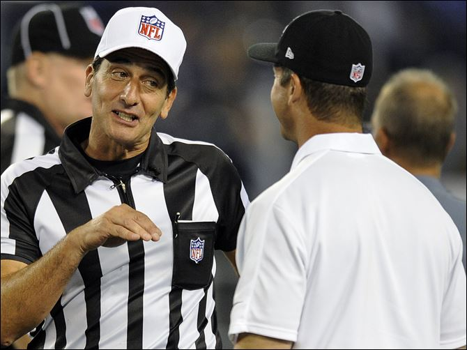 Referee Gene Steratore, left, talks with Baltimore Ravens head coach John Harbaugh before Thursday's game in Baltimore.