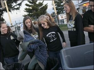 Arielle Moehling, 16, center, places a donated jacket in a collection bin before the start of Friday evening's home game against Sylvania Southview. The athletic department and student council sponsored the event 'Jackets Giving Jackets.' Students and residents alike were encouraged to bring a new or used jacket to the game for donation.