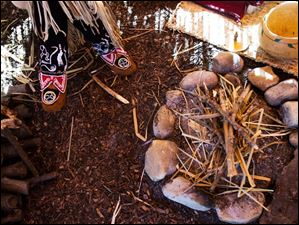Linette Torbet, of Wauseon, sits inside the wigwam she built while speaking with people attending Saturday's event.