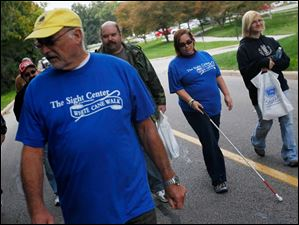 Tammy Belman, of Wauseon, center right, walks alongside her husband, Todd, center left, and her niece Abby Brink, 19, right, The Belman family came out for the event to support The Sight Center because of the work they had done to help Tammy after she lost most of her sight during an operation.
