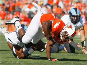John Pettigrew, 20, is tripped up by University of Rhode Island player Andrew Bose, 52, during the first quarter.