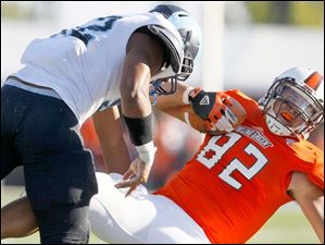 Alex Bayer is hit by University of Rhode Island's Andrew Bose during the second quarter.