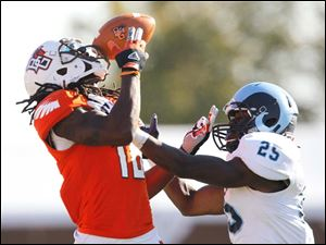 BGSU's Je'Ron Stokes can't catch the ball as it hits him in the face mask as URI's player Johnny Joseph defends on the play.
