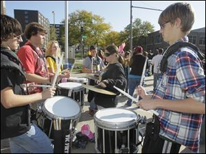 Clockwise, from left: Matt Phillips, a sophomore, seniors Brad Eisenmann and Liz Feltz, sophomore Nick Bartlett [fourth from left and facing camera], sophomore Christina Howard on the cymbals, and Garrett Weddington, a sophomore, of the Northview High School Marching Band, keep the beat for their bandmates and marchers at the event.