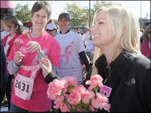 Martha Daum, of Maumee, left, receives a survivors' carnation from Leah Stoltenberg, 19, an Ohio Northern University student from Pittsburgh.