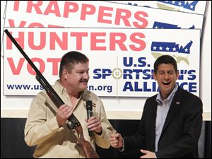 David Dlubak, owner of the Ithaca Gun Company, presents Republican vice presidential candidate, Rep. Paul Ryan, R-Wis., with a special edition Romney/Ryan Ithaca shotgun before Ryan speaks to the U.S. Sportsmen's Alliance annual banquet Saturday in Columbus. A Romney/Ryan logo was engraved on the stock of the gun.