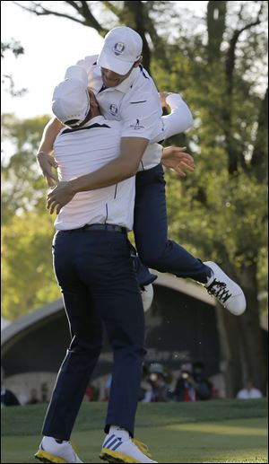 Europe's Martin Kaymer leaps into the arms of teammate Sergio Garcia after winning the Ryder Cup PGA golf tournament Sunday.