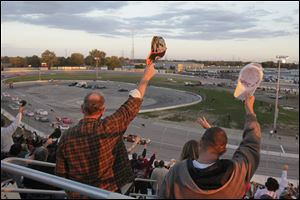 Fans raise their hats to the drivers at the start of Saturday night's race at Toledo Speedway. The fans in attendance were treated to a wild finish.
